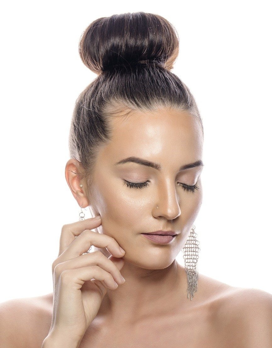 woman clear skin and hair up in bun