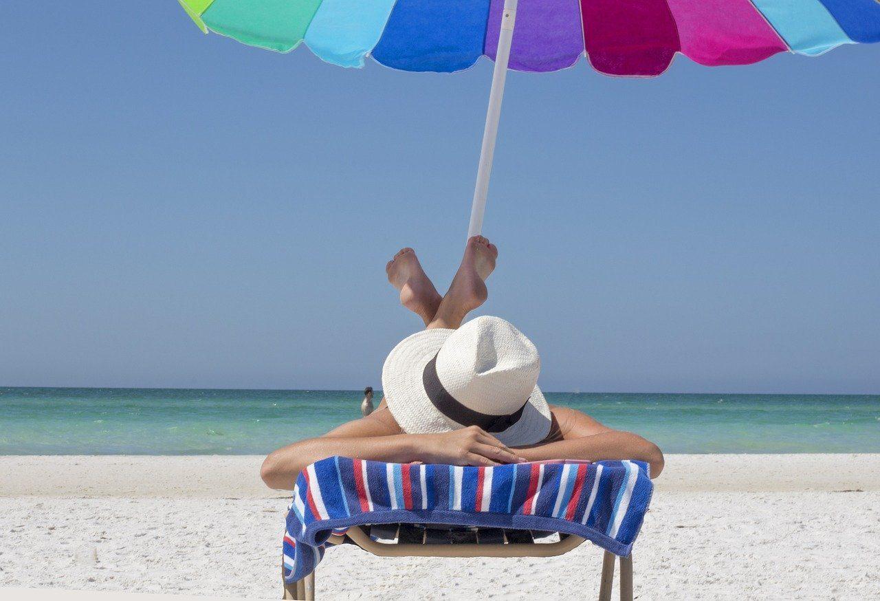 woman sitting in sun on beach vitamin d